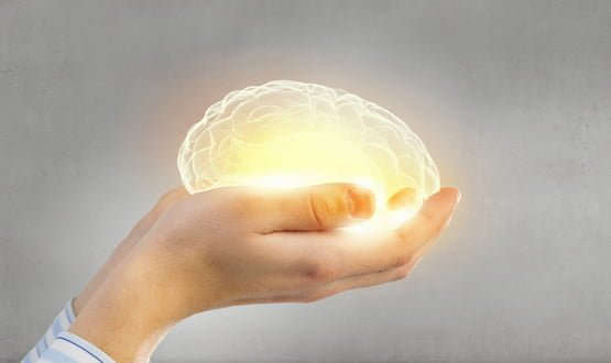 Hands cradling a glowing brain