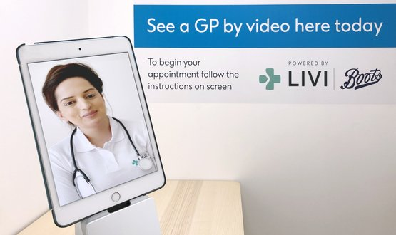 A female GP from Livi appears on a tablet computer in a Boots consultation room