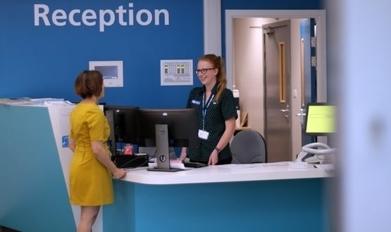 Healthcare staff speaks to a female patient at the reception of Sheffield Teaching Hospitals