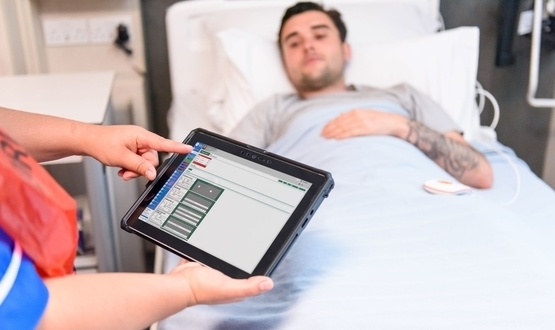 A nurse examines a electronic patient chart on a tablet